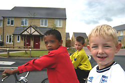 Boys playing on bicycle on Housing Association estate; Halifax; Yorkshire UK
