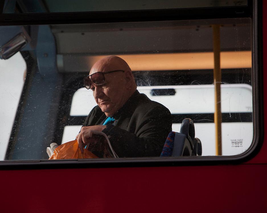 A man on a London Bus looking through his bag
