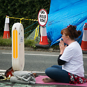 Anti-fracking  activists and protesters outside the gates of Quadrilla's fracking site June 31st, Lancashire, United Kingdom. A woman pray outside the police cordon in the street. The struggle against fracking in Lancashire has been going on for years. The fracking company Quadrilla is finally ready to bring in a drill tower to start drilling and anti-frackinhg activists are waiting in front of the gates to block the equipment getting in.