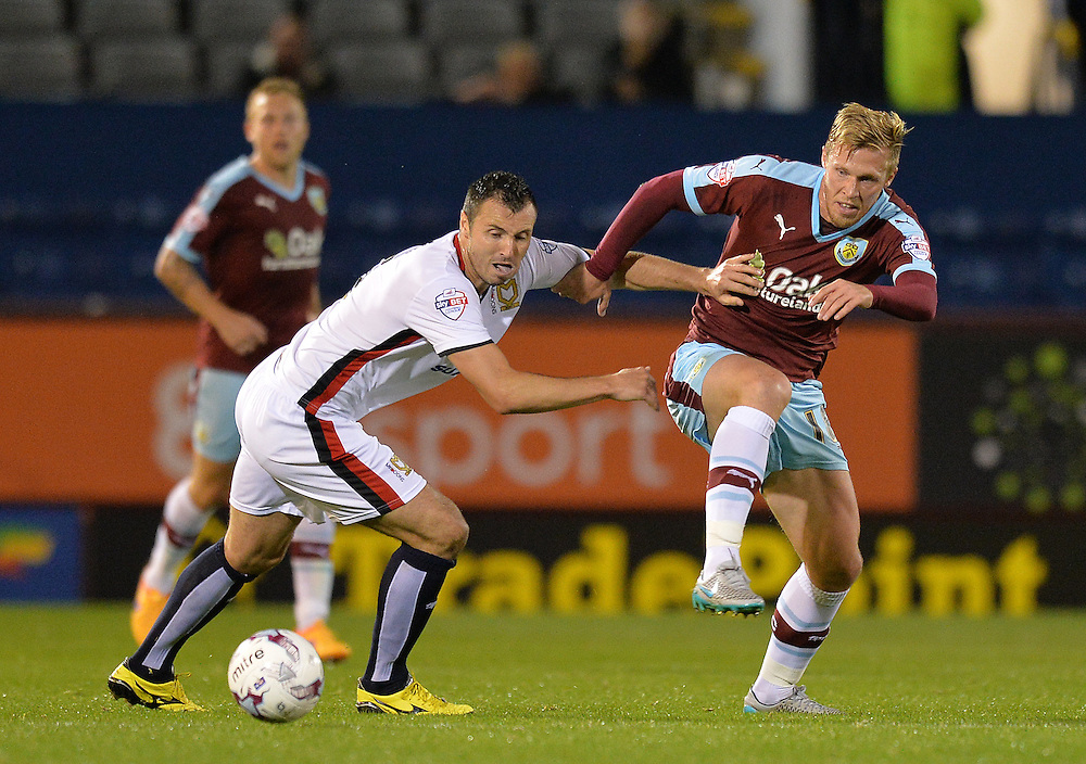 Burnley's Rouwen Hennings is tackled <br /> <br /> Photographer Dave Howarth/CameraSport<br /> <br /> Football - The Football League Sky Bet Championship - Burnley v Milton Keynes Dons - Tuesday 15th September 2015 - Turf Moor - Burnley<br /> <br /> © CameraSport - 43 Linden Ave. Countesthorpe. Leicester. England. LE8 5PG - Tel: +44 (0) 116 277 4147 - admin@camerasport.com - www.camerasport.com