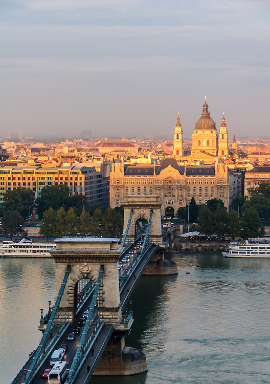 The Chain Bridge, Gresham Palace, and St. Stephen's Basilica in Budapest, Hungary. The bridge connects Széchenyi square on the Pest side and Clark Ádám Square in Buda side.