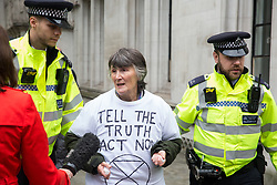 London, UK. 17 October, 2019. Metropolitan Police officers arrest one of eight activists from Trident Ploughshares who had glued themselves together outside the Supreme Court during a protest by activists from the XR Peace group of Extinction Rebellion to highlight the Government's continuing failure to respect international law regarding arms sales on the 11th day of International Rebellion Autumn Uprising protests.
