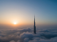Aerial view of Burj Khalifa Tower in a sea of clouds at sunset in Dubai, United Arab Emirates.