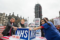 London, UK. 25 November, 2019. Activists wearing Donald Trump and Boris Johnson masks fight for control of the NHS with NHS doctors including Sonia Adesara during a protest by campaigners from Keep Our NHS Public, Health Campaigns Together, We Own It and Global Justice Now in Parliament Square to call on Prime Minister Boris Johnson to end privatisation of healthcare in the National Health Service (NHS).