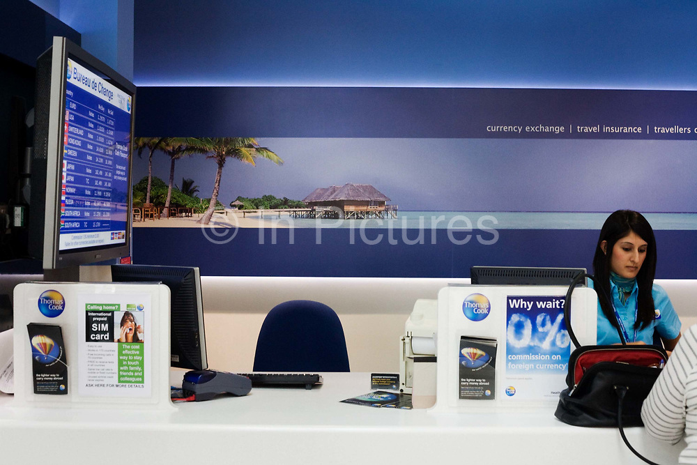 """A female member of the Thomas Cook staff issues foreign currency to an unseen airline passenger in the departures concourse at Heathrow Airport's Terminal 5. This Bureau de Change is one of two companies trading in foreign exchange, travel insurance and travellers cheques for passengers passing through this aviation hub is west London. We see on the wall behind the assistant, a beach paradise scene of palm trees, calm seas and beach chalets, the idea of tranquillity and prosperity. On the left are the exchange rates for the world's currencies for purchase at this kiosk. From writer Alain de Botton's book project """"A Week at the Airport: A Heathrow Diary"""" (2009)."""