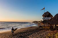Las Penitas  , Nicaragua - Febuary 21 , 2018 :   surfers walking on the beach at sunset in Léon  Nicaragua