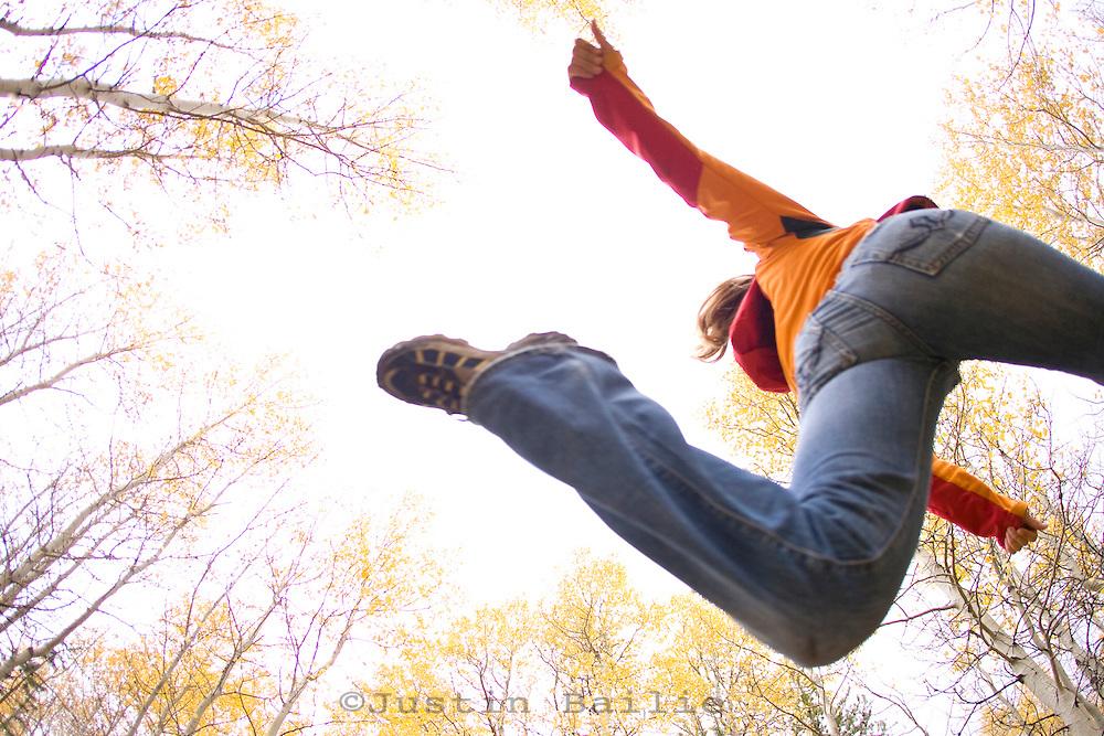 Young woman jumping through aspens during fall near Fallen Leaf Lake, CA.