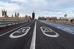 © Licensed to London News Pictures. 30/12/2020. LONDON, UK.  The Houses of Parliament stand behind a pair of 20 miles per hour speed limit signs on the road on Westminster Bridge which, together, show the year 2020.  As 2020 draws to a close, MPs are due to ratify the UK/EU trade deal in Parliament today.  At the same time, the UK government is trying to tackle the effects of the record levels of coronavirus cases which may require an increase in national tier alert levels.  Photo credit: Stephen Chung/LNP
