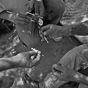 Mexican heroin addicts prepare needles for injecting the drug along the Tijuana River in Mexico..(Credit Image: © Louie Palu/ZUMA Press).July 2012