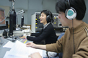 """Radio announcers Li Ming laughs (L) with her colleague Xie Yu (R) as they read the news for the radio program """"Kejia Xiangqing"""" in Kejia, or Hakka language in Beijing November 19."""