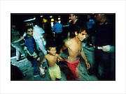 Kosovar Romani refugee boys arrive at Italian port, after a passage by Mafia boat across the Adriatic. Roma were accused of accomplice with the Serbs. Hundreds of thousands of Roma were ethnically cleansed from Kosovo after the war. Brindisi, Italy summer 1999. ..Roma Gypsies left Rajasthan in India a thousand years ago, in the ninth and tenth centuries. They were pushed west by the Ottoman Muslim Empire as it moved through Persia towards the frontiers of Europe. They entered Europe in the foutrteenth century and were slaves in Romania and Moldavia until the mid 1850s. There are about 15 million Roma gypries in the world, about 12 million who live in Europe. they are Europe's largest ethnic minority. They have rich traditions and culture, their own language. They are renowned for their prowess in music and dance; they are also skilled craftsman, metal roofmakers, silver and goldsmiths. Their traveling and nomadic lifestyle which grew from a necessity to find work, and because they were often moved on from one place to the next, has given them both a liberty but also marks them as different and they are often feared by sedentary peoples, who label and scapegoat them. They are hardy survivors and live in the brunt of racism and prejudice, often marginalised, living in poverty, without proper human rights afforded to them..