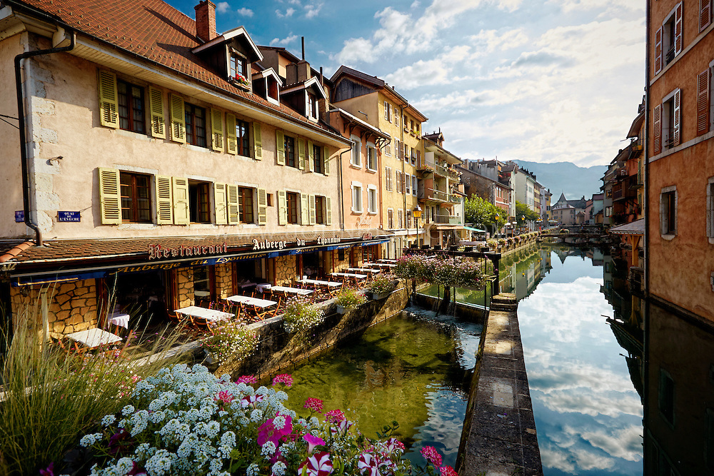 View of the Auberge du Lyonnais Hôtel/Restaurant and other buildings along the incredible reflective waters of the Thiou Canal, Old Town Annecy, France.