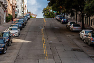 San Francisco, CA, USA -- January 23, 2016. Photo looking up to the top of a a very hilly street with cars parked in all the available parking spaces in San Francisco, California.