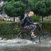 Foto: David Rozing Nederland Barendrecht 29 mei 2018 Wateroverlast door enorme hoosbuien clusterbui clusterbuien hoosbui. Jonge meid op fiets fietser fietst door ondergelopen straten. Code Oranje