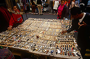 A stallholder keeps an eye on a buyer at his collection of watches at Bermondsey market, south London, England. A spread of wristwatches and other time-pieces of all ages and styles are laid out on a table surface. In the background are other visitors to this famous market where unusual, if pricey, purchases can be found. Officially called New Caledonian Market, Bermondsey Market is an antiques market located at Bermondsey Square on Tower Bridge Road in Bermondsey, part of the London Borough of Southwark, in South London, England. The location was formerly the site of Bermondsey Abbey.