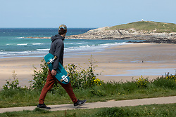 "© Licensed to London News Pictures. 11/05/2020. Newquay, UK. A man walks with a skateboard near Fistral beach on the North coast of Cornwall, the day after British Prime Minister Boris Johnson announced a 'road map' to lift lockdown restrictions due to Covid-19, (Coronavirus). A rise in ""staycations"" - the concept of holidaying in your home country rather than travelling abroad - is expected, with many visitors planning to visit Cornwall. However, an ongoing campaign titled ""#ComeBackLater"" is trying to persuade tourists not to visit the county until it is safe to do so. Photo credit : Tom Nicholson/LNP"
