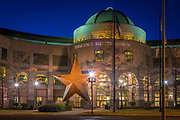 """The Bullock Texas State History Museum, is a history museum in Austin, Texas. The museum is a division of the Texas State Preservation Board. Its stated mission is to tell """"the Story of Texas."""" The history museum is named after former Texas Lieutenant Governor Bob Bullock, who championed its creation. The museum is located at 1800 North Congress Avenue in Austin, a few blocks north of the Texas State Capitol. The museum has three floors of interactive exhibits; the first floor theme is """"land,"""" the second floor theme """"identity,"""" and the third floor theme """"opportunity."""" On the second floor of the museum, 'The Spirit Theater' host a feature presentation entitled 'Star of Destiny.' Designed by award winning experience designer Bob Rogers (designer) and the design team BRC Imagination Arts, the special effects theater presentation takes audiences on an epic journey through the history of Texas, narrated by the character of Sam Houston. In addition to playing several shows, daily, the 200 seat Texas Spirit Theater is also used by the museum as a multimedia special effects theater for alternate film and lecture presentations The museum also has a 70mm film-based IMAX theater. The theater seats 400 and has a projector with both 2-D and 3-D capability."""