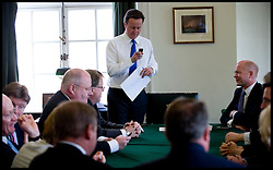 David Cameron checks his phone as he holds a Shadow Cabinet meeting in his office in Norman Shaw South on the day Labour announced it will be holding talks to form a coalition Government with the Liberal Democrats, May 10, 2010. Photo By Andrew Parsons / i-Images