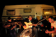 """Ricao Balliardo plays gitan music with his family, in his camping arund the fire. Saintes Maries festival<br /><br />""""Le Pelerinage des Gitans""""; the French gypsy pilgrimage of Saintes Maries de la Mer, Camargue, France<br /><br />Sainte Sara is an uncannonized saint, who legend says looked after the Christian Saints Marie Jacobe and Marie Salome, cousins of Mary Magdalene, who arrived, it is said, on the shores of the Camargue in a rudderless boat. Saint Sara is the patron saint of gypsies who come from far and wide to see her. There are even paintings of Sara as 'Kali' the black saint in Eastern Europe. Sara may have been the priestess of 'Ra' the sun-god or even servant girl to the Christian saints. No-one really knows.<br /><br />For a few weeks of the year, Roma, Gitan and Manouche gypsies come from all over Europe in May, camping in caravans around Saintes Maries de la Mer. It is a festive time where they play music, dance, party and christen their children. They all go to see Saint Sara in the crypt, kissing or touching her forehead. Many put robes on her shoulders, making her fat for the procession. In the main Gypsy procession of the 24th May, Saint Sara is allowed to leave her crypt, beneath the church, and is carried from the church to the shores of the mediterranean and back again. One day a year she is free from her prison. Hundred's of years ago the Gypsies used not even to be allowed into the church, only into the crypt like Sara...<br /><br />Roma gypsies still suffer oppressive prejudice and racism and are one of the ethnic groups the most persecuted and marginalised across Europe. The festival is one of the times where they celebrate with people of all races, their faith and traditions"""