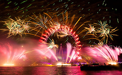 © Licensed to London News Pictures. 01/01/2014. London, UK. Fireworks explode at the London Eye in central London just after midnight to mark the start of the New Year on 1 January 2014. Large crowds lined the banks of the River Thames for the New Year eve celebration, which for the first time ever included multi-sensory fireworks that can be smelt and tasted. Photo credit : Vickie Flores/LNP.