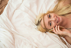 Portrait of a beautiful young woman talking on smart phone in the bedroom, Bavaria, Germany