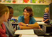 A teacher smiles while working with two of her students during class