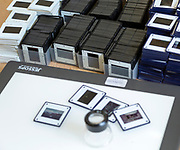 Piles of film transparency slides and Lightbox with viewing enlarger loupe