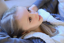 Teenage girl relaxing and daydreaming on couch