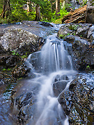A small waterfall cascades with a silky blur in Box Canyon on the hike to Rachel Lake in Alpine Lakes Wilderness, Wenatchee National Forest, Washington, USA