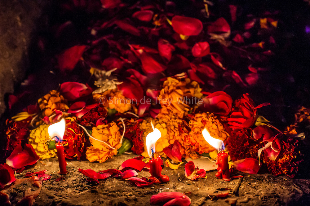 """8th January 2015, New Delhi, India.Three red candles burn in front to of a mound of flower petals left by believers hoping to get wishes granted by Djinns in the ruins of Feroz Shah Kotla in New Delhi, India on the 8th January 2015<br /> <br /> PHOTOGRAPH BY AND COPYRIGHT OF SIMON DE TREY-WHITE a photographer in delhi<br /> + 91 98103 99809. Email: simon@simondetreywhite.com<br /> <br /> People have been coming to Firoz Shah Kotla to leave written notes and offerings for Djinns in the hopes of getting wishes granted since the late 1970's. Jinn, jann or djinn are supernatural creatures in Islamic mythology as well as pre-Islamic Arabian mythology. They are mentioned frequently in the Quran  and other Islamic texts and inhabit an unseen world called Djinnestan. In Islamic theology jinn are said to be creatures with free will, made from smokeless fire by Allah as humans were made of clay, among other things. According to the Quran, jinn have free will, and Iblīs abused this freedom in front of Allah by refusing to bow to Adam when Allah ordered angels and jinn to do so. For disobeying Allah, Iblīs was expelled from Paradise and called """"Shayṭān"""" (Satan).They are usually invisible to humans, but humans do appear clearly to jinn, as they can possess them. Like humans, jinn will also be judged on the Day of Judgment and will be sent to Paradise or Hell according to their deeds. Feroz Shah Tughlaq (r. 1351–88), the Sultan of Delhi, established the fortified city of Ferozabad in 1354, as the new capital of the Delhi Sultanate, and included in it the site of the present Feroz Shah Kotla. Kotla literally means fortress or citadel."""