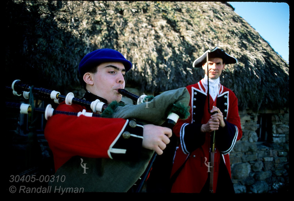 Young man dressed as Jacobite soldier plays bagpipes beside Old Leanach Cottage as a Redcoat soldier watches; Culloden, Scotland.