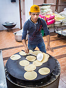 "08 FEBRUARY 2015  BANGKOK, THAILAND: A man cook chapatis (unleavened Indian flatbread) on a griddle in the kitchen before the communal meal at the Gurdwara Siri Guru Singh Sabha in Bangkok. Thailand has a small but influential Sikh community. Sikhs started coming to Thailand, then Siam, in the 1890s. There are now several thousand Thai-Indian Sikh families. Gurdwara Siri Guru Singh Sabha was established in 1913. Construction of the current building, adjacent to the original Gurdwara (""Gateway to the Guru""), started in 1979 and was finished in 1981. The Sikh community serves a daily free vegetarian meal at the Gurdwara that is available to people of any faith and background.    PHOTO BY JACK KURTZ"