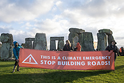 Salisbury, UK. 5th December, 2020. Climate activists hold a banner calling for an end to new road building during a Mass Trespass at Stonehenge. The trespass was organised in protest against the approval by Transport Secretary Grant Shapps of a £1.7bn project for a two-mile tunnel beneath the World Heritage Site and a further eight miles of dual carriageway for the A303, as well as the government's £27bn Road Investment Strategy 2 (RIS2).