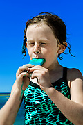 Girl eating a popcicle at the beach.