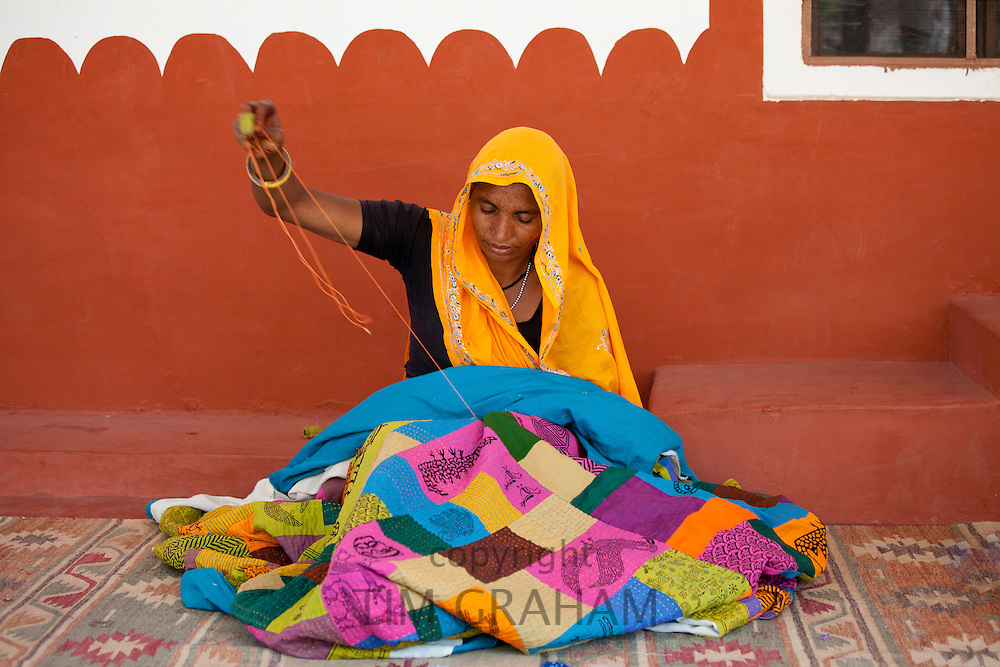Indian woman sewing textiles at Dastkar women's craft co-operative, the Ranthambore Artisan Project, in Rajasthan, India