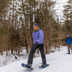 A couple snowshoeing at Western Foothills Land Trust's Twin Bridges Preserve in Otisfield, Maine.