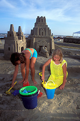 Stock photo of two young girls building a large sand castle on the beach