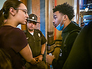 15 JUNE 2020 - DES MOINES, IOWA: MATTHEW BRUCE, a leader of Black Lives Matter in Des Moines (right) talks to a member of the Governor's staff while a State Trooper guards the door of the Governor's Reception Room in the Iowa capitol in Des Moines. About 75 supporters of Black Lives Matter marched through the Iowa capitol Monday to demand the restoration of voting rights for felons who have completed their sentences. Iowa is one of only two states in the US that permanently strip felons of voting rights. The issue is a  racial one in Iowa. Blacks make up only 4 percent of the population but 25 percent of the prison population. The Governor agreed to meet with a delegation of the protesters but she would not commit to immediately restoring voting rights. She said would draft an executive order to restore voting rights later in the summer.      PHOTO BY JACK KURTZ