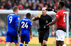 Leicester City's Jamie Vardy (left) receives a yellow card from Referee Mike Dean during the Premier League match at the King Power Stadium, Leicester.