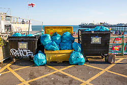 © Licensed to London News Pictures. 25/06/2020. Brighton, UK. Bags of rubbish are left near bins on the beach in Brighton and Hove as thousands of visitors took to the seaside resort on the hottest day of the year. Photo credit: Hugo Michiels/LNP