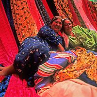 Uygar women relax in an outdoor fabric shop they run in a bazaar near Kashgar (Kashi), a town on the ancient Silk Road in Xinjiang, China.