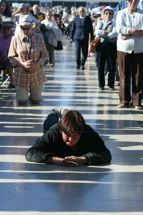 A pilgrim crawls along the pavement in front of the Catholic Fatima shrine in central Portugal 13 October 2006. Thousands of pilgrims converged on Fatima to celebrate the anniversary of the first apparition of the Virgin Mary to three shepherd children on 13 May 1917.PHOTO PAULO CUNHA/4SEE