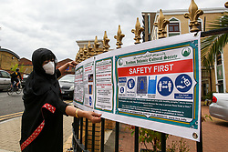 © Licensed to London News Pictures. 06/07/2020. London, UK. Mrs Bibi Khan, president of London Islamic Cultural Society and Mosque wearing a face covering displays a sign on the railing of the Mosque. Wightman Road Mosque, also known as London Islamic Cultural Society and Mosque, in north London, prepares to open after the COVID-19 lockdown, by placing a number of measures required by law for worshippers. The government announced that gatherings of more than 30 worshippers are allowed for acts of communal worship in churches, synagogues, mosques, temples and other places of worship. All worshippers attending Mosques will have to wear face coverings and bring their own prayer mat, Quran, and a reusable shoe bag. Photo credit: Dinendra Haria/LNP