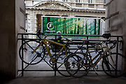 Parked bikes and passing truck with an image of sunlit forestry and eco recyclig theme amid the reality of capital city.