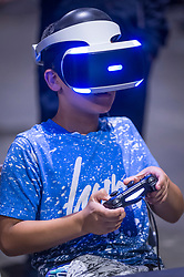 © Licensed to London News Pictures. 12/08/2018. LONDON, UK. A boy plays on a virtual reality machine at Play Expo London, a video games show featuring consoles, handhelds, computers, vintage arcades and pinball machines, organised by Replay Events taking place at the Printworks in Canada Water, East London.  Photo credit: Stephen Chung/LNP