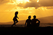 Couple and young daughter watch the sunset in Honolulu