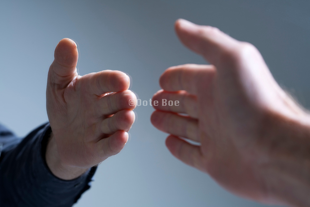 reaching out to shake hands with your own mirror image