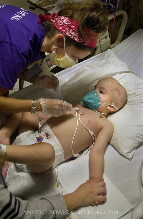 Tommy Bennett, 3, endures the cleaning of his intravenous lines to avoid infection by nurse Amanda Lescher at Duke University Medical Center, where he is living in an isolation ward for children with life-threatening diseases.  November 26, 2002