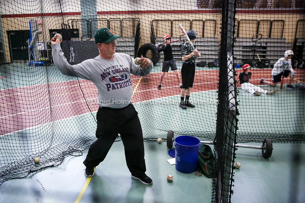 (4/5/17, HOPKINTON, MA) Guidance counselor and baseball coach, Keith Verra, throws some balls for a hitter in the batting cage during practice at Hopkinton High School on Wednesday. [Daily News and Wicked Local Photo/Dan Holmes]