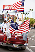 10 APRIL 2006 - PHOENIX, AZ: People wave American flags from the back of a pickup truck during an immigration demonstration in Phoenix, AZ. More than 125,000 people participated in a march for immigrants's rights in Phoenix Monday. The march was a part of a national day of action on behalf of undocumented immigrants. There were more than 100 such demonstrations across the US Monday.  Photo by Jack Kurtz